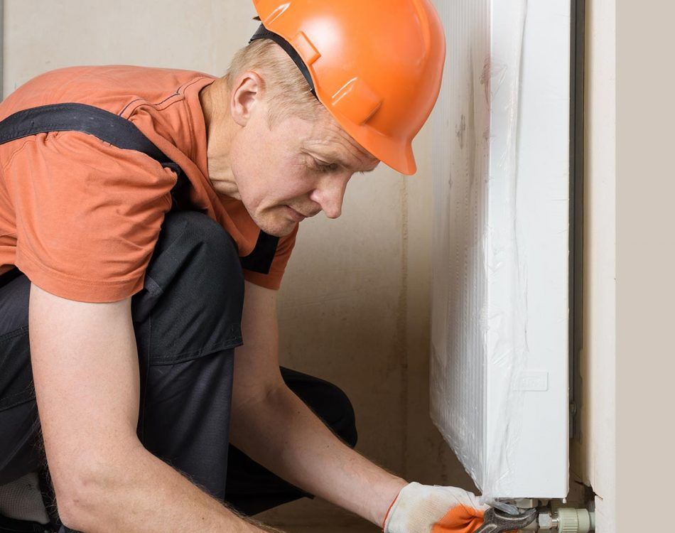 plumber-attaching-pipes-heating-system-radiator